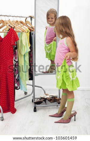 Little girl trying on large shoes standing in front of mirror - stock photo