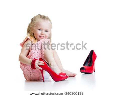 Little girl trying on mummy's shoes isolated - stock photo