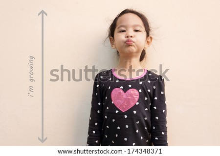 Little girl trying to be taller - stock photo