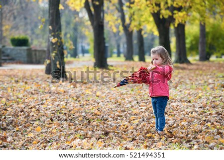 Little girl trying to open umbrella in the autumn park.Copy space