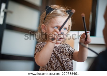 Little girl trying to paint her father - stock photo