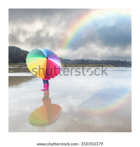 """Little girl turned away from the lens with a rainbow umbrella.  Rainbow reflection in surrounding water.  """"Rainbow Days"""" - stock photo"""