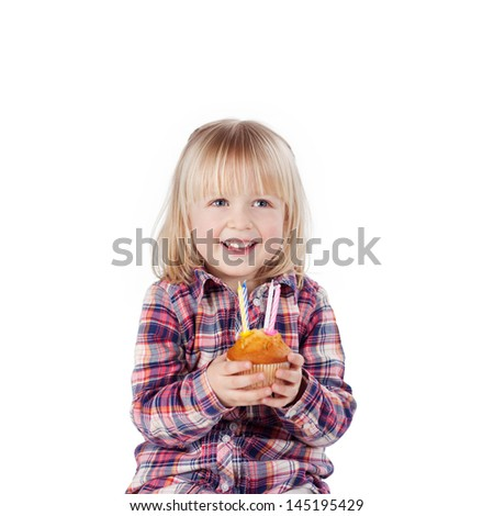 Little girl turning four years old grinning happily as she holds a little birthday cake with candles in her hands - stock photo