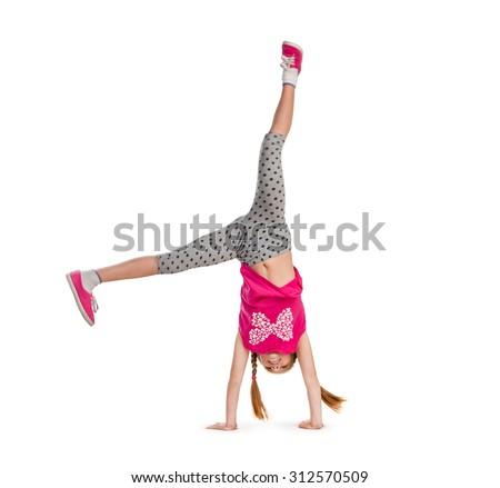 little girl turning handsprings in a studio - stock photo