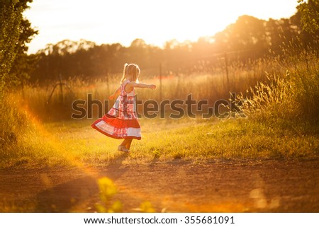 Little girl twirling in the sun - stock photo