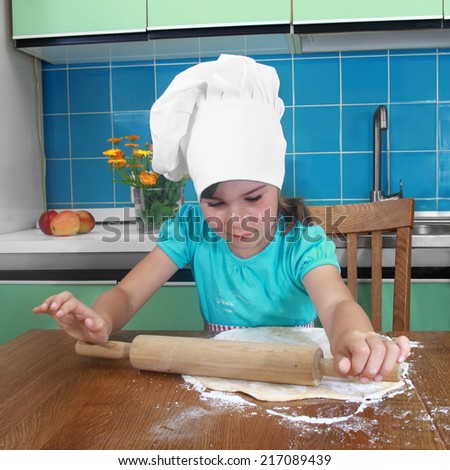Little girl unrolls the dough on table in the kitchen - stock photo