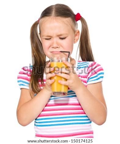 Little girl unwillingly drinking orange juice using straw, isolated over white - stock photo