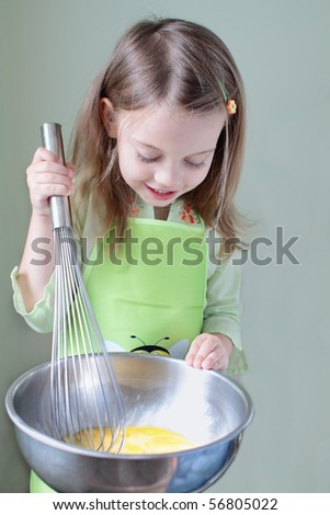 Little girl uses an extra large whisk to beat eggs for breakfast. Some motion blur on whisk where little girl is beating eggs.