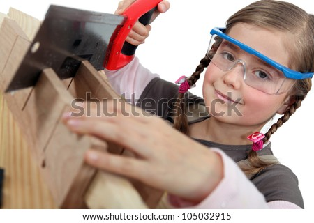 Little girl using a hand saw - stock photo