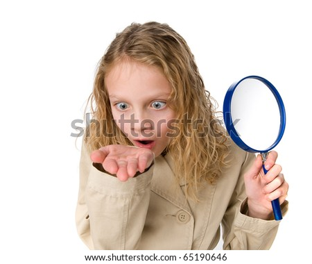 Little girl using a magnifying glass - stock photo