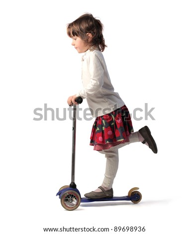 Little girl using a scooter - stock photo