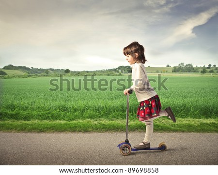 Little girl using a scooter on a countryside road - stock photo