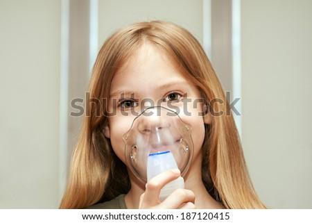 Little girl using an inhaler indoors - stock photo