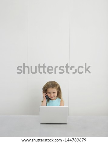 Little girl using cellphone and laptop at desk