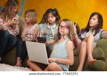 Little girl using laptop while her friends are busy playing on video game consoles - stock photo