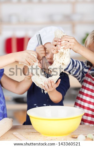 Little girl using whisk on dough while siblings holding it at kitchen counter - stock photo