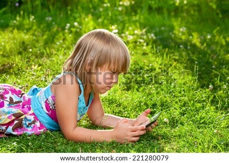 Little girl usng a touch pad in a summer garden - stock photo