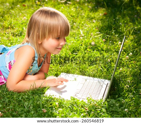 Little girl usng laptop in a summer garden - stock photo