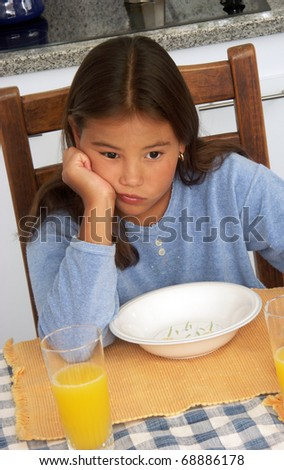 Little girl waiting for her breakfast at kitchen. - stock photo