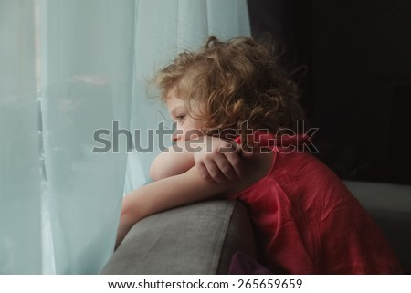 Little girl waiting for someone and looking out the window - stock photo
