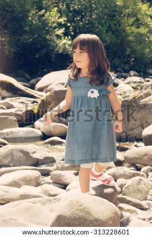 Little girl walk over the stones in the river