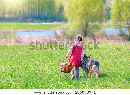 Little girl walking and going to picnic with dog back to camera - stock photo