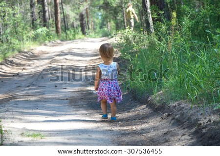 Little girl walking away by the field road in the forest - stock photo