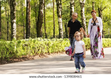 Little girl walking by the park road with parents holding hands going behind