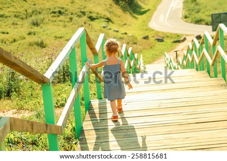 Little girl walking down stairs. View from the back. - stock photo