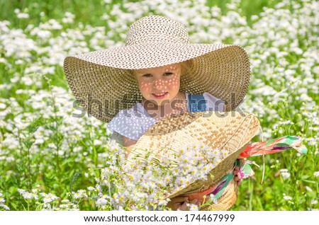 Little girl walking in the field with daisies - stock photo
