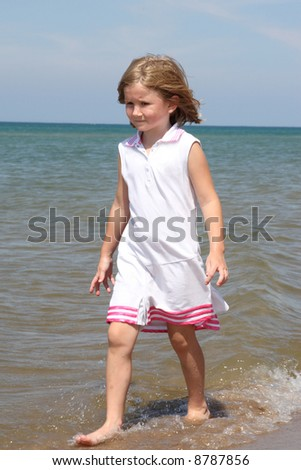 Little girl walking on the beach on a warm summer day