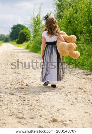 Little girl walking on the road in summer. Back to camera.