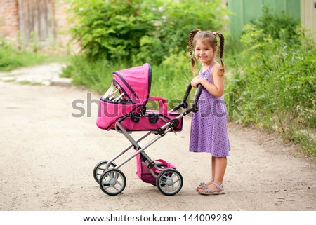 Little girl walking with a toy stroller in an urban neighborhood. Little Mama. - stock photo