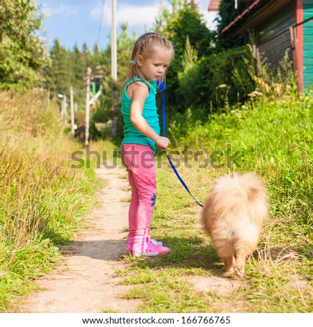 Little girl walking with her dog on a leash