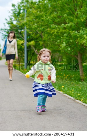 Little girl walks in the park with her mother in the spring