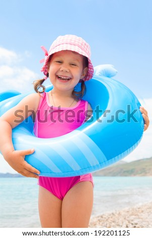 little girl wants to swim with inflatable whale on the sea - stock photo