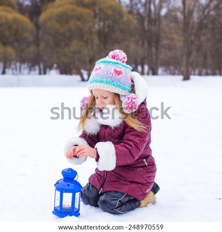 Little girl warms hands on candle in lantern outdoors - stock photo