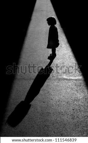 Little girl was standing in the sun between two shadows which enabled me to photograph a beautiful silhouette with a long shadow - stock photo