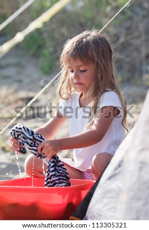 Little girl washes clothes with her hands - stock photo