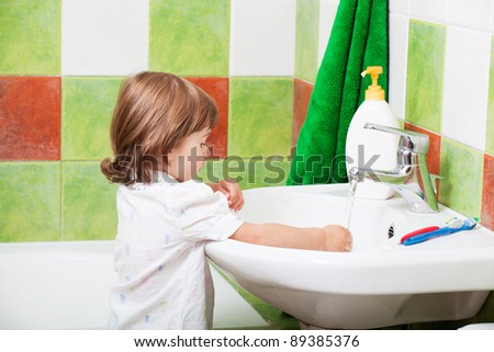 little girl washes in a bathroom