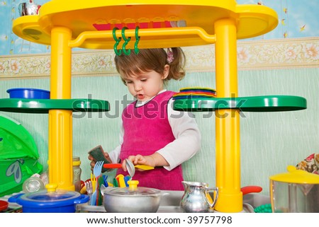 little girl washes ware - stock photo