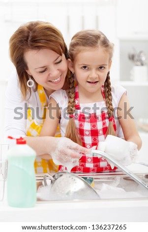 Little girl washing dishes helped by her mother - closeup - stock photo