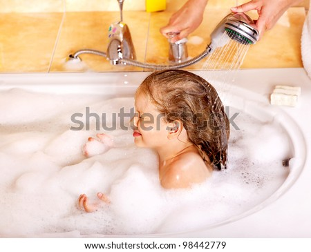 Little girl washing hair in bubble bath.