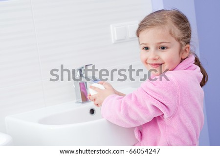 Little girl washing hands in bathroom - stock photo