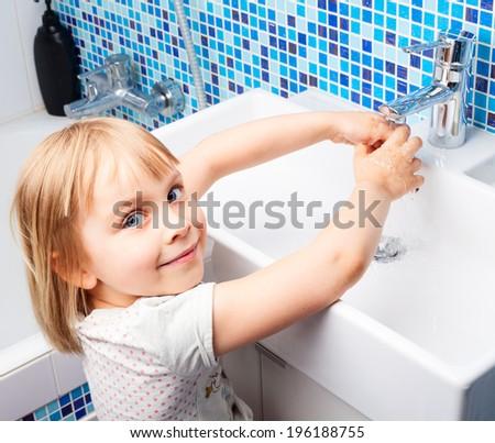 Little girl washing her hands in bathroom sink - stock photo