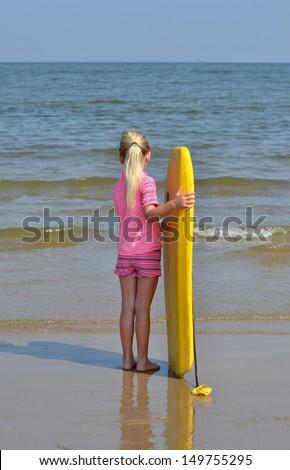 little girl watching ocean waves - stock photo