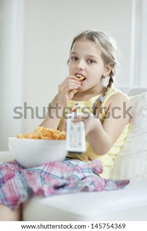 Little girl watching TV as she eats wheel shape snack pellets - stock photo