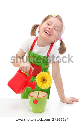 Little girl watering a  daisy plant with a watering can toy