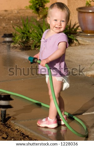 little girl waters using a hose - stock photo