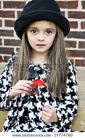 Little girl wearing a coat and hat holding a flower - stock photo